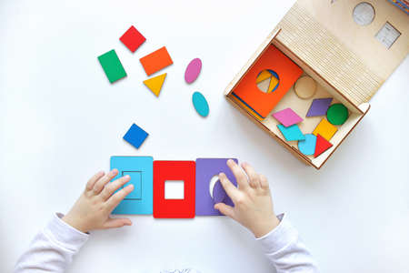 Learning colors and shapes. Childrens wooden toy. The child collects a sorter. Educational logic toys for kids. Childrens hands close-up. Montessori Games for Child Development