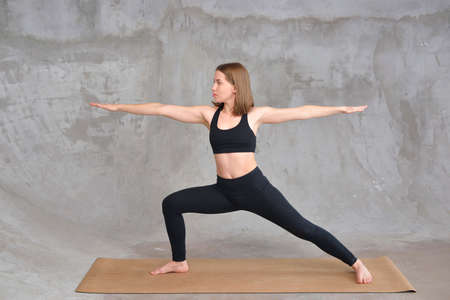 brown-haired woman in black sportswear on a gray concrete background in sitting in a yoga and meditation position. Woman meditating in lotus pose. Concept of relaxation. Recreation and harmony