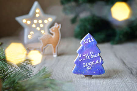 four Christmas gingerbread in glaze in the form of bulls, Christmas symbols 2021, on a white table with New Year's decor, horizontal
