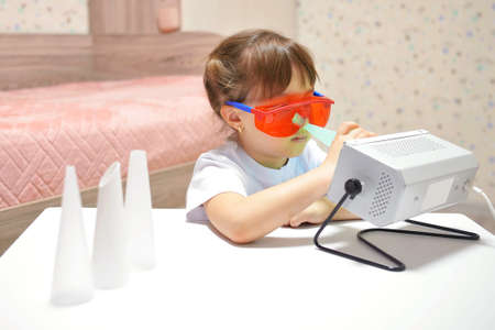 the girl cleans her nose with the Antibacterial ultraviolet quartz lamp to prevent the body from bacteria and coronavirus pandemic viruses. Child health care