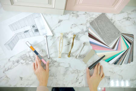 Home improvement concept. Girl the designer chooses the facades and handles for cabinet furniture in a store showroom. decors boards on the furniture industry. Choosing samples of materials.