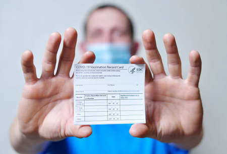 male is holding a vaccination record card and corona virus vaccine vials. Passport of immunity to the coronavirus in the hands of a male. Health passport as proof of recovery from COVID-19