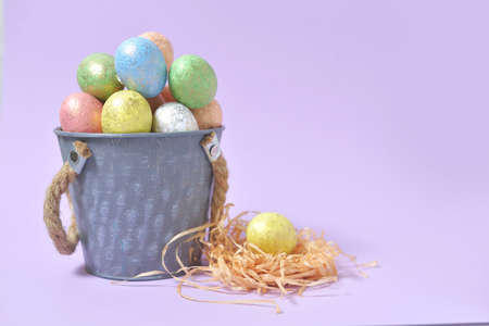 Colorful Easter eggs on a soft purple background in a gray bucket in the style of minimalism. with place for text. Easter background. High quality photo 版權商用圖片
