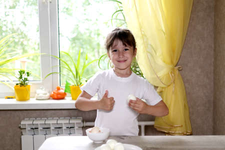 lifestyle preschooler child girl cook food in the kitchen. development of fine motor skills in everyday life from scrap materials. child cleans eggs Stock fotó