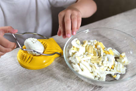 lifestyle preschooler child girl cook food in the kitchen. development of fine motor skills in everyday life from scrap materials. the child cuts the eggs with a yellow egg cutter