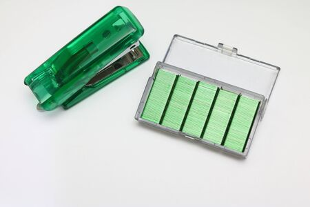 green Stapler and pin on a white background.