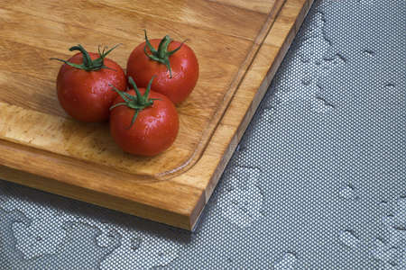 Three fresh tomatoes in the kitchen. Chopping board. Stock Photo - 5179448