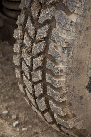 All terrain tire coated in mud  Detail of an off-road vehicle photo
