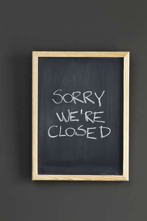 opening hours: Closed  Store sign on black board Stock Photo