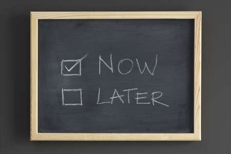 later: Now and later check boxes written on a blackboard