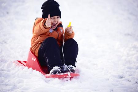 enfant garçon donnant thumbs up, jouer et rire sur pied d'hiver enneigé dans la nature. Givre season.Focus d'hiver sur les pouces donnant jusqu'à Banque d'images