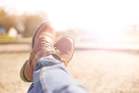 cross legs: Cross Legs with walking shoes on  blurred background during sunny summer day