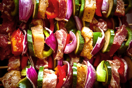spit: Orderly rows of meat on wooden spits.Various colorful and healthy vegetables grill in a barbecue. Shish kebabs made with mushrooms,peppers,cherry tomatoes,zucchini,onions.Pattern