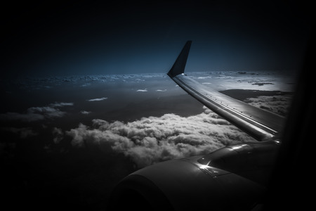 filming point of view: View from window of plane an airplane during night.Wing airplane view sunset, sunset sky clouds night.Wing of the on skyat night.Wing of plane on airplane flying above the clouds background .view from the window of a of the wing,