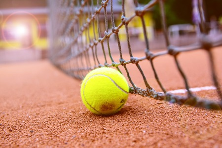 tennis ball on a tennis court with blurred background.
