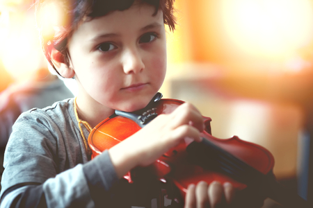Child playing the violin in the room Reklamní fotografie