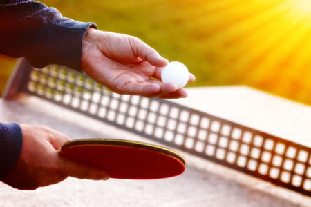 Close up of tennis player hands with tennis racket on nature background in sunny day.Closeup shot of a man serving in table tennis. Outdoor tennis table play.Sport concept