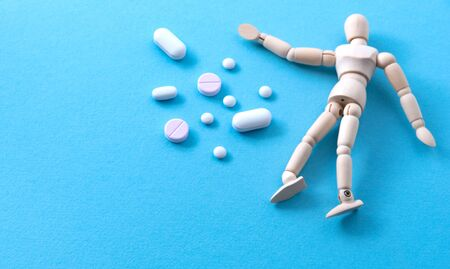 Heap of pills near miniature wooden human model at blue background. Harmful effects of medications concept