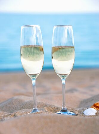 Romantic evening on beach with two glasses of champagne against blue sea. Фото со стока