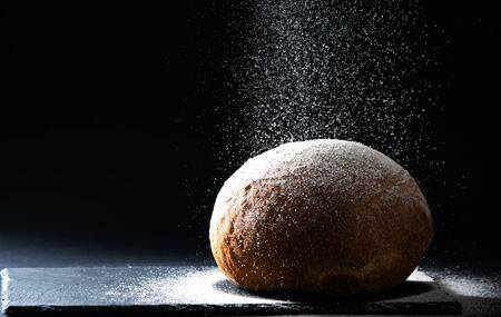 Close up bread with falling flour on black background. Bread making concept, copy space, horizontal.