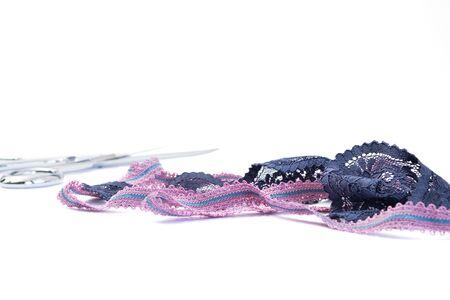 Deux bandes de dentelle de couleur purpur et bleu et des ciseaux de tailleur flous à l'arrière-plan. Notion de couture. Mise au point sélective, espace pour le texte
