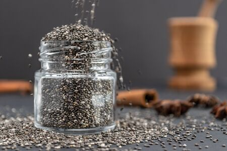 Pouring dry chia seeds in glass jar with unfocused objects on background. Copy space. Paleo diet, chia superfood concept. Imagens