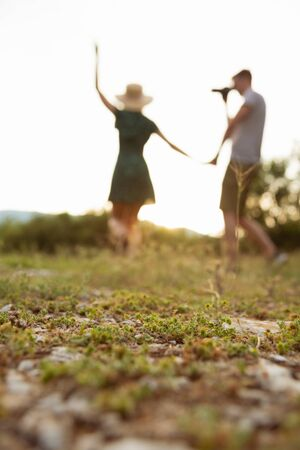 Silhoette of couple walking at field holding hands while man photoshooting a woman. Selective focus