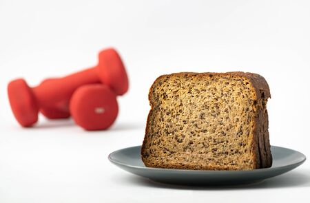 Fitness protein bread and unfocused red dumbbells on background. Helthy lifestyle sports concept.