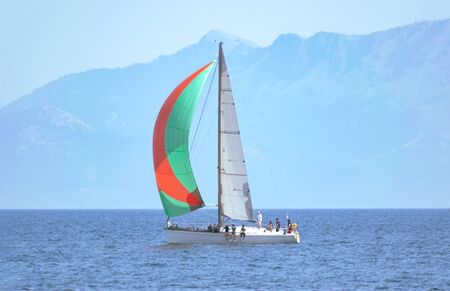 Sailing yacht with colorful sail in open sea at day with island at background. Yachting adventure concept 写真素材