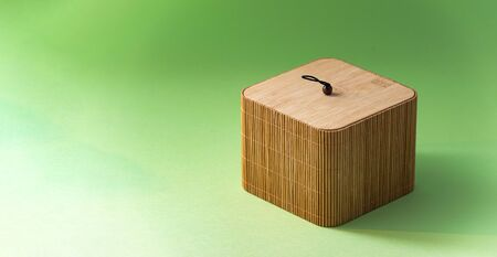 Closed bamboo box on green background with copy space.