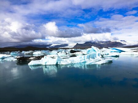 Photo of a broken off glacier part in the glacial lagoon of Jökulsárlón, in the south of Iceland, with some reflections in the water on a lightly overcast day