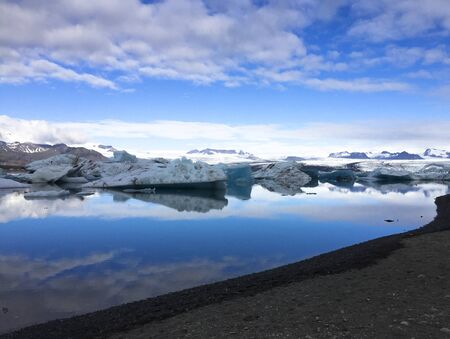 Photo of a broken off glacier part in the glacial lagoon of Jökulsárlón, in the south of Iceland, with some reflections in the water on a lightly overcast day Stock Photo - 135411667
