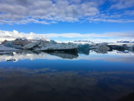 Photo of a broken off glacier part in the glacial lagoon of Jökulsárlón, in the south of Iceland, with some reflections in the water on a lightly overcast day Stock Photo - 135411738