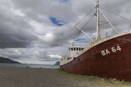 An out-of-the-way whaling ship that rusts on the road to Látrabjarg on a dead cloudy day. The shipwreck has the identification BA 64 and is located on a beach in the west of Iceland