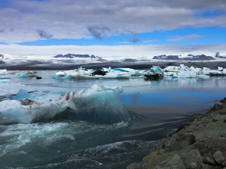 Photo of a broken off glacier part in the glacial lagoon of Jökulsárlón, in the south of Iceland, with some reflections in the water on a lightly overcast day Stock Photo - 135411817