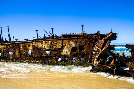 Photograph of the shipwreck of the SS Maheno on Fraser Island with a cloudless sky in the background. Fraser Island is located off Queensland in eastern Australia Stock Photo