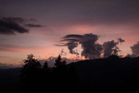 A silhouette before a colorful sunset after a thunderstorm in the Swiss Alps Imagens
