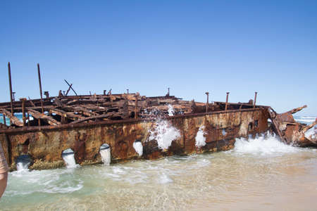 Photograph of the shipwreck of the SS Maheno on Fraser Island with a cloudless sky in the background. Fraser Island is located off Queensland in eastern Australia