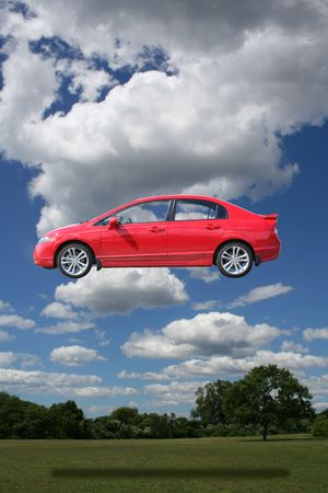 free thought: bright red compact car enjoying beautiful day in park Stock Photo