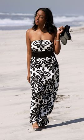 woman barefoot: african american woman in black and white dress walking on the beach