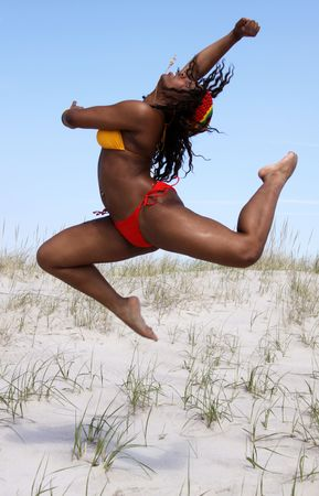 sexy girl dance: african american woman leaps across beach
