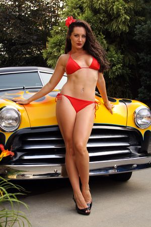 pin up model posing with flamed hot rod photo