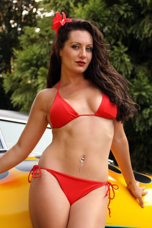 retro woman: pin up model posing with flamed hot rod