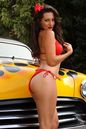 custom car: Pin up model posing with flamed hot rod