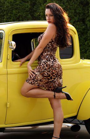 cola mujer: pines hasta modelo posando con amarillo hot rod Foto de archivo