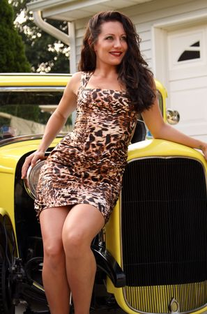 Pin up model posing with yellow hot rod