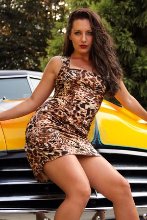 Pin up model posing with vintage hot rod photo