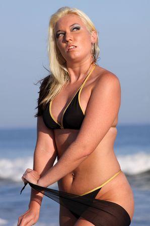 thong bikini: blond in black thong bikini posing on beach