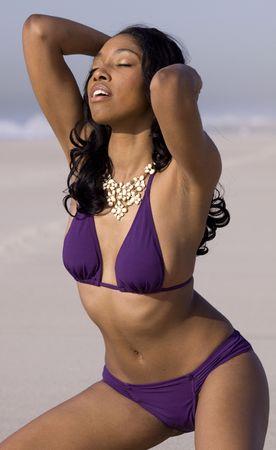 african american woman posing in bikini on a beach