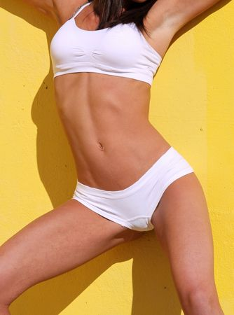 tanned body: toned and tanned body against a yellow wall